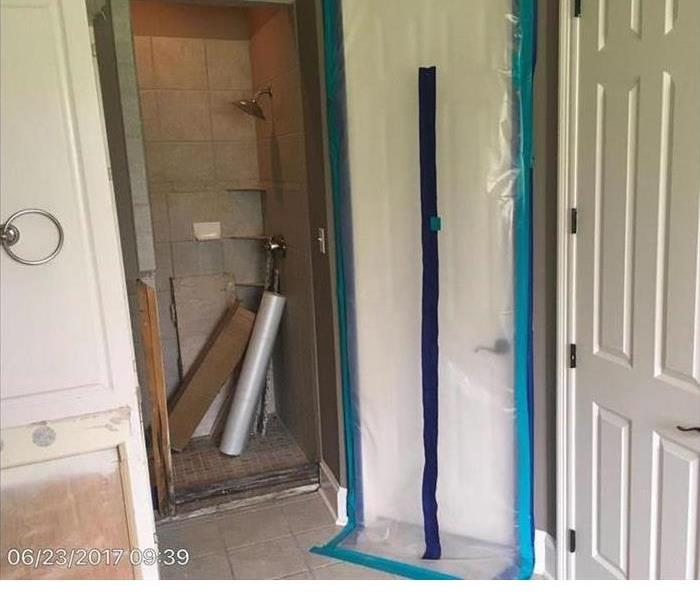 A taped off door in a mold impacted bathroom