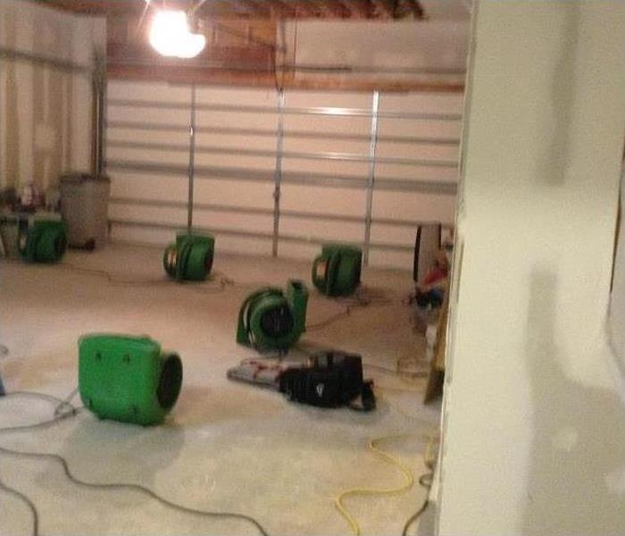 a room that had been damaged by water with green servpro air movers in it