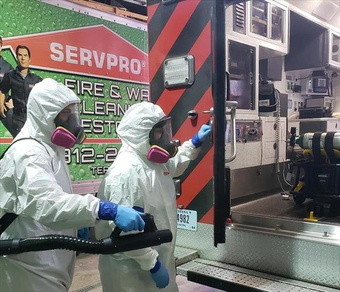 SERVPRO employees in full hazmat gear helping to clean a fire engine